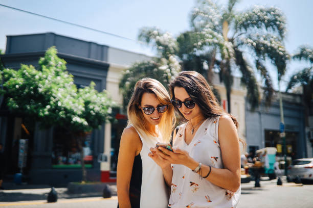 Two women looking at the smartphone in Buenos Aires stock photo
