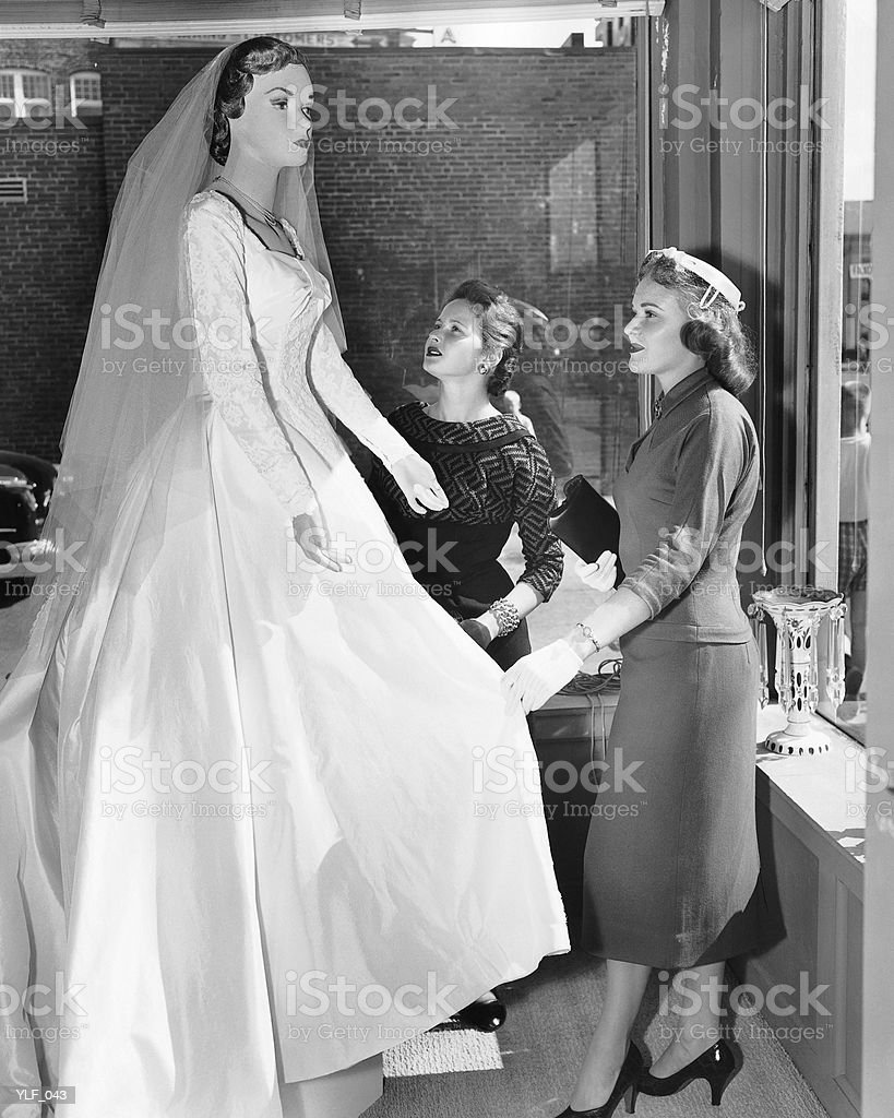 Duas mulheres olhando no vestido de noiva manequim em foto royalty-free
