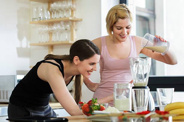Zwei Frauen, die einen Mahlzeitenersatz-Shakes – Foto