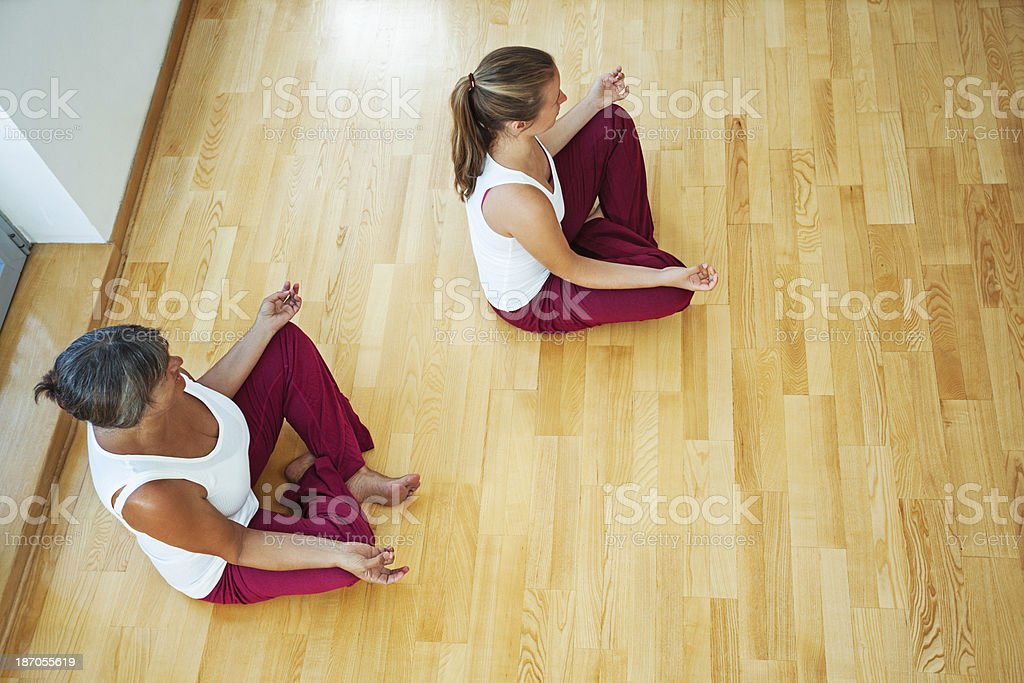 Two women meditate at home royalty-free stock photo