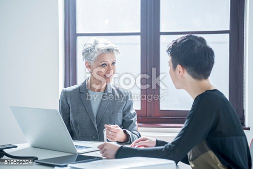 istock Two women meeting in modern office with laptop 519522324