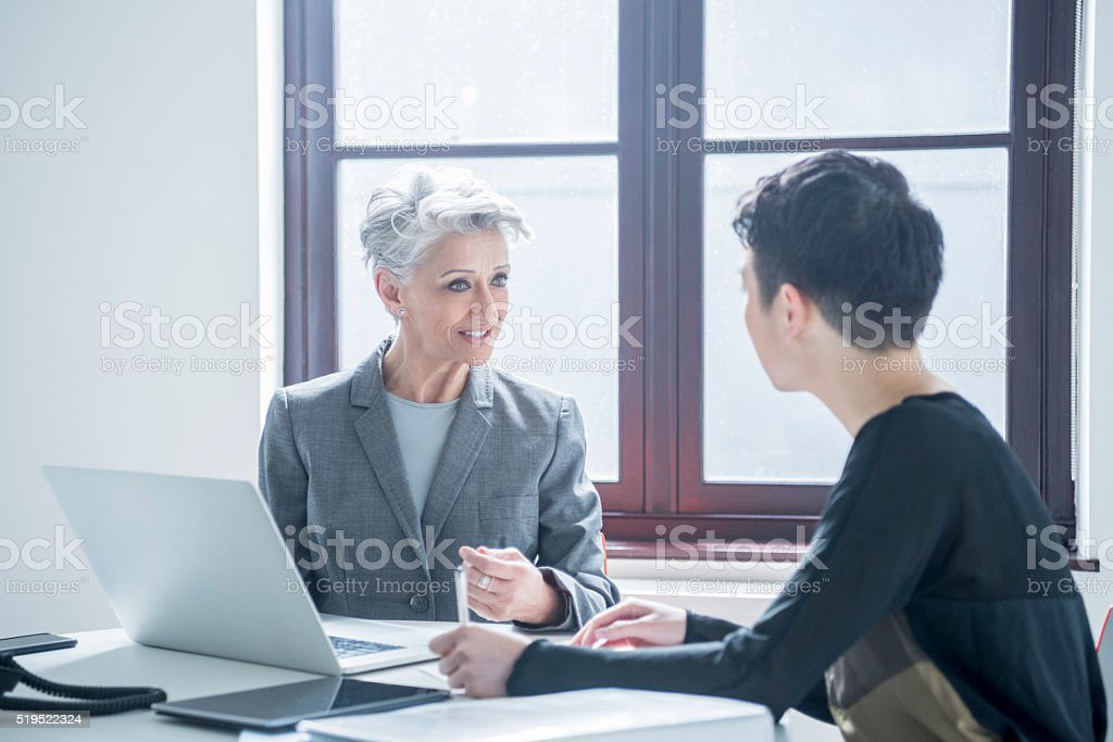 Two women meeting in modern office with laptop stock photo