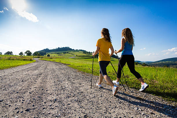Two women Nordic walking down a gravel road with scenic view Two women exercising nordic walking stock pictures, royalty-free photos & images