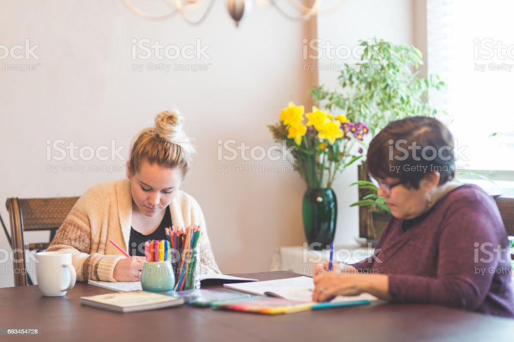 Two women of different ages drawing in adult coloring books  at table stock photo