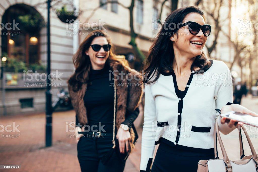 Two women on city street having fun stock photo