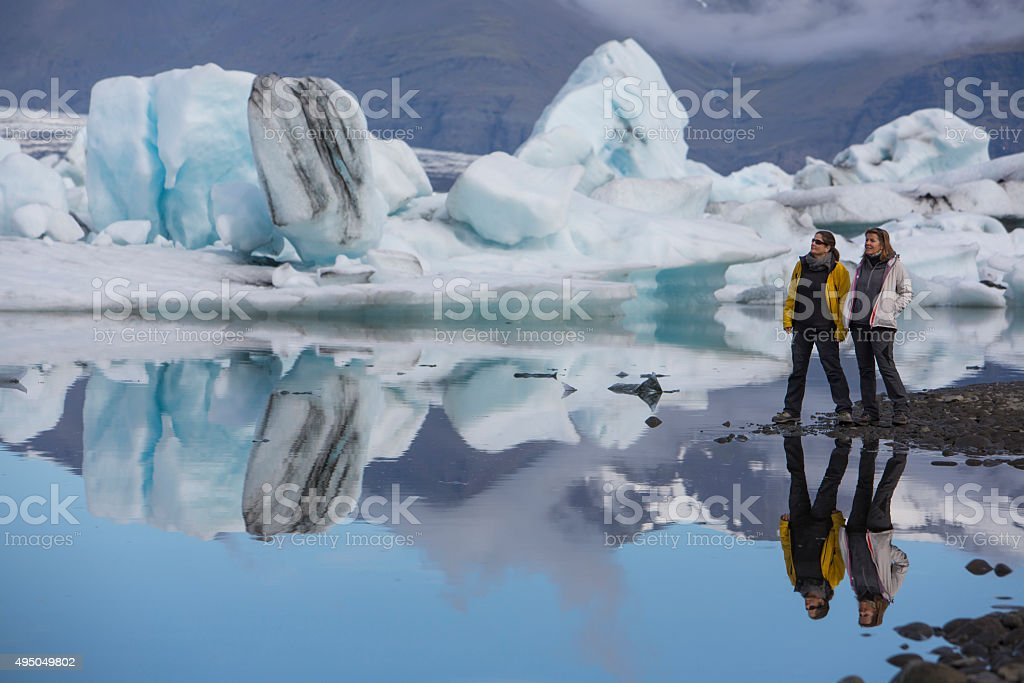 two women on glacier lagoon jokulsarlon in iceland stock photo