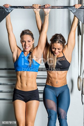 Vertical color image of two women having fun during tough exercise on gymnastic bar.