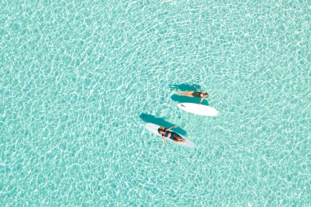 two women on paddle board in blue ocean - laguna foto e immagini stock