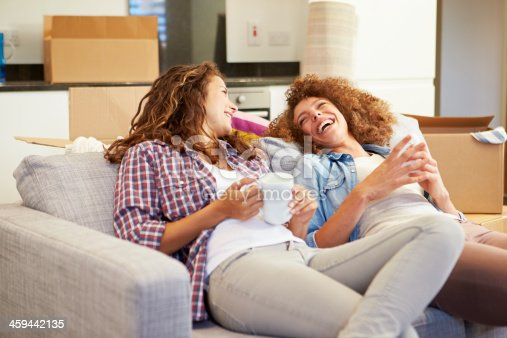 istock Two Women On Sofa With Hot Drink In New Home 459442135