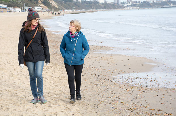 Two women one older and one younger walking on beach stock photo