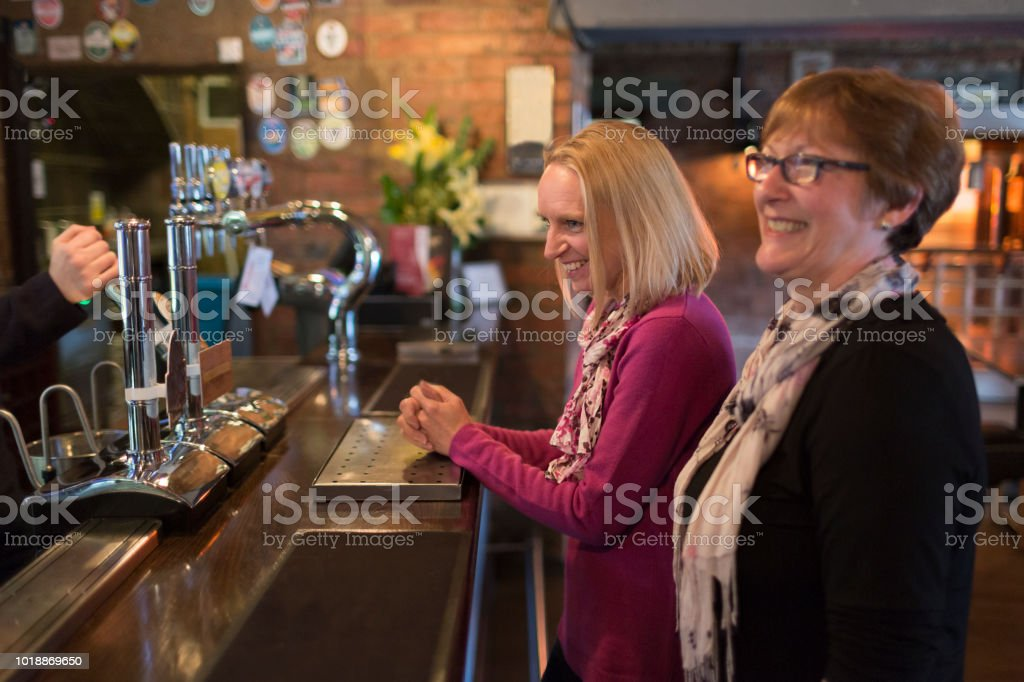 Two women ordering drinks in a restaurant bar stock photo