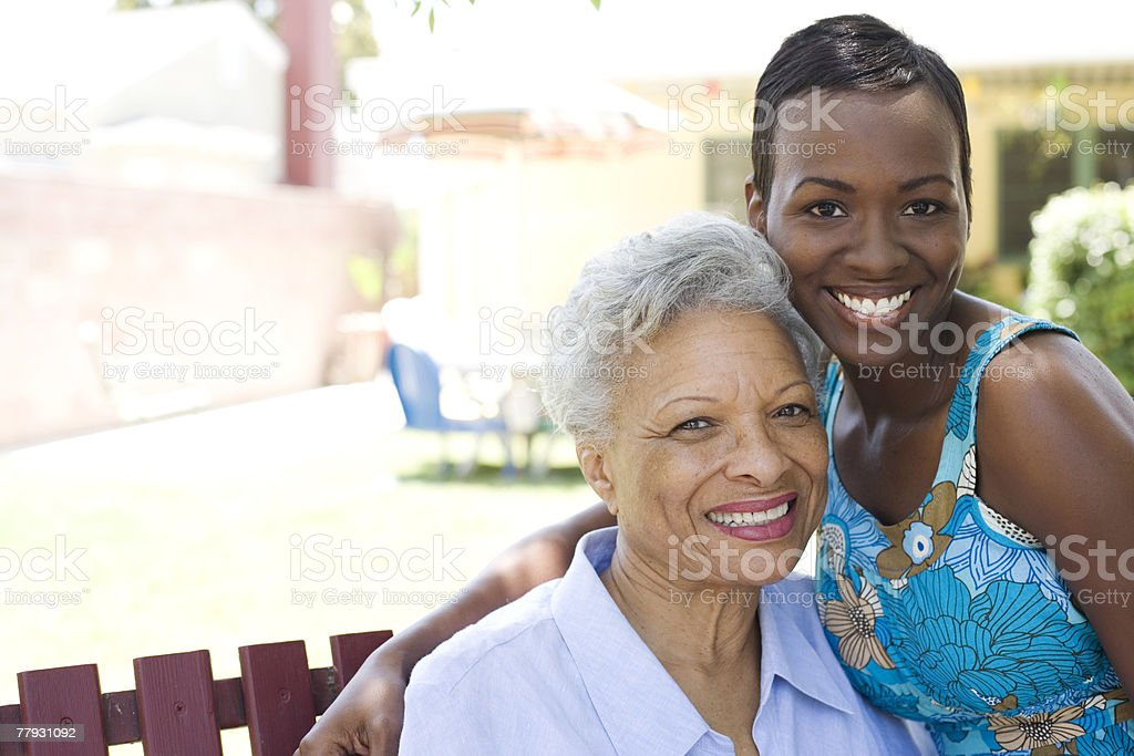Two women outdoors on wooden bench stock photo