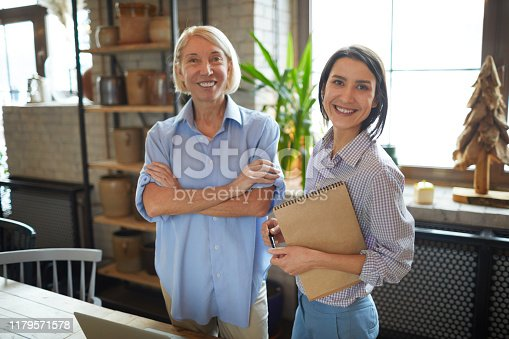 Waist up portrait of two female entrepreneurs posing in workshop of small business company, copy space