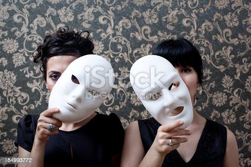 istock Two women peeking behind mask on wallpaper background 184993772