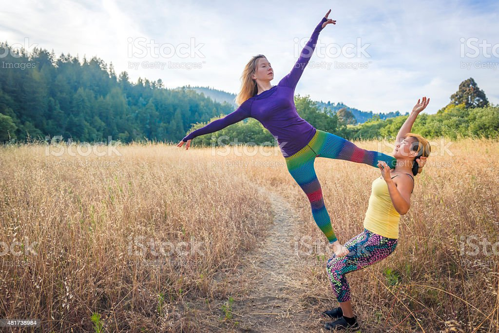 Two women performing an acro-yoga pose in a field. stock photo