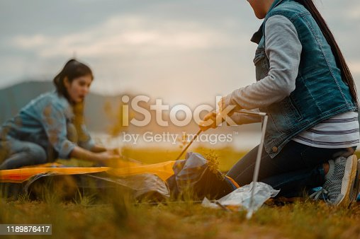 Two women pitching tents for camping On Camping Holiday.