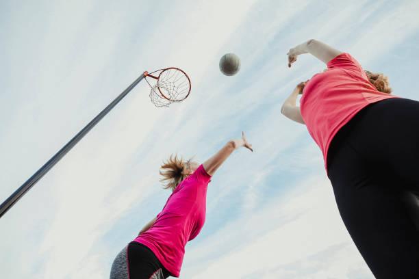 twee vrouwen spelen netball - netball stockfoto's en -beelden