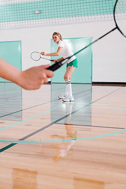 dos mujeres jugando bádminton - bádminton deporte fotografías e imágenes de stock
