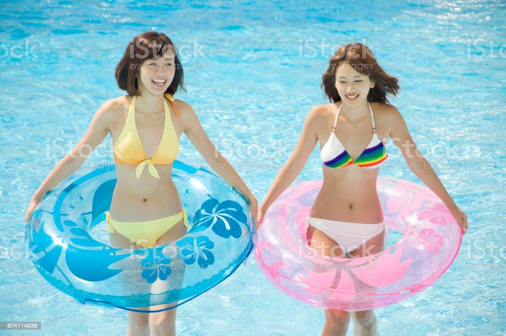 兩名女人彈在浮泳裝在游泳池 免版稅 stock photo