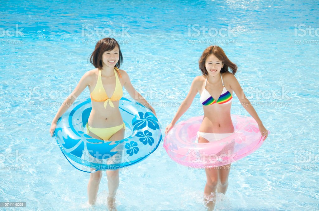 Two women playing in the pool with float swimsuit royalty-free stock photo