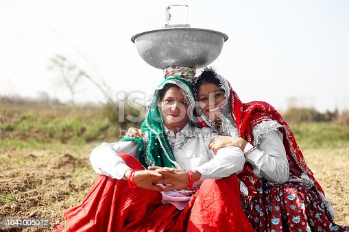 Two women of Indian ethnicity portrait together outdoor in nature. The both are wearing traditional Indian clothes.