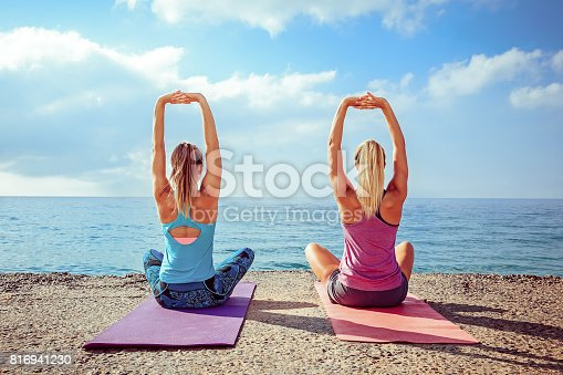 816941230 istock photo Two women practicing stretching exercises at the beach 816941230