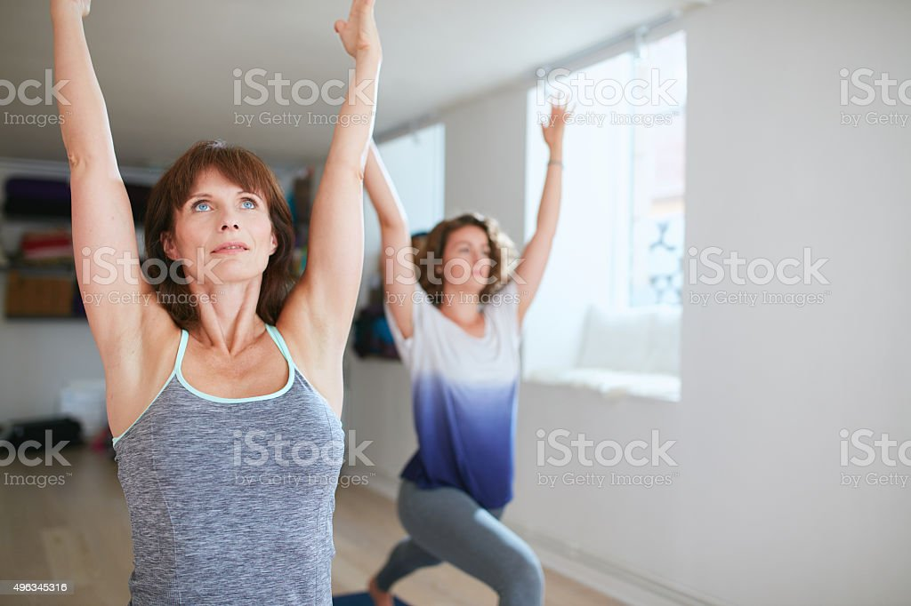 Two women practicing yoga forms at class stock photo