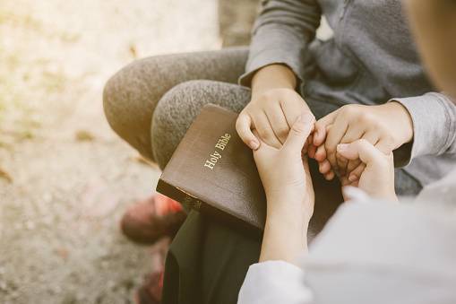 two women pray on the bible.