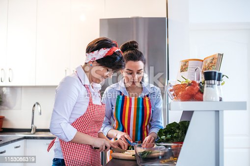 Two young cute caucasian women preparing a salad in domestic kitchen together.