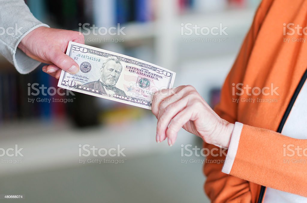 Two women pulling on a banknote stock photo