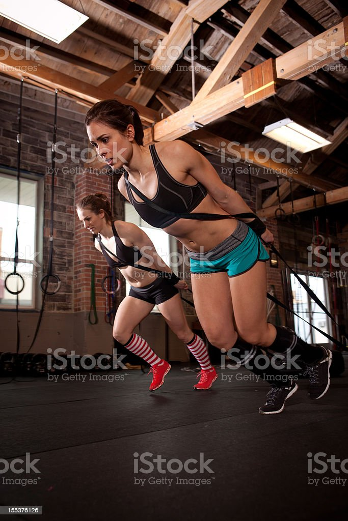 Two women pulling weighted sleds during a gym workout royalty-free stock photo