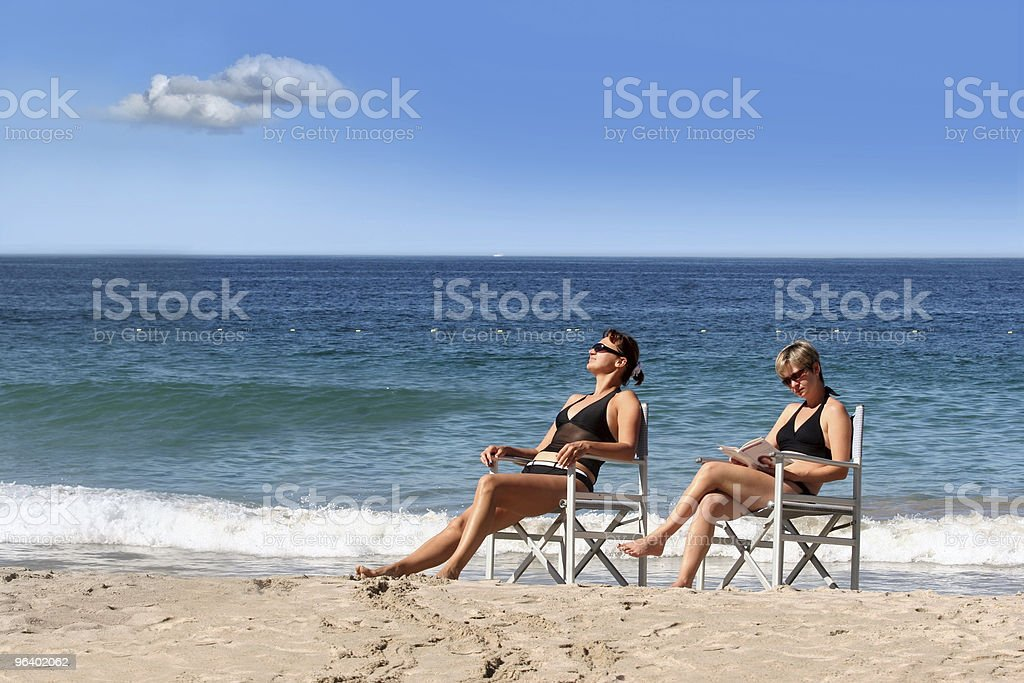 Two women reading on the beach - Royalty-free Adult Stock Photo