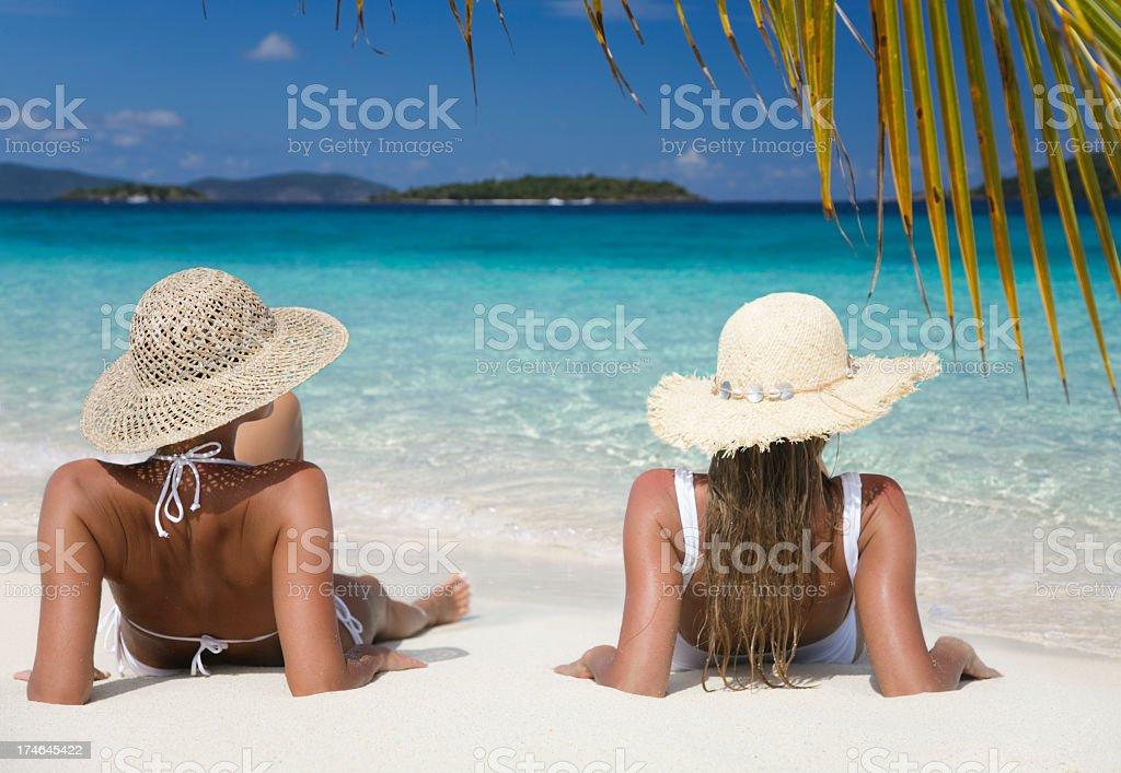 two women relaxing on beautiful tropical beach royalty-free stock photo