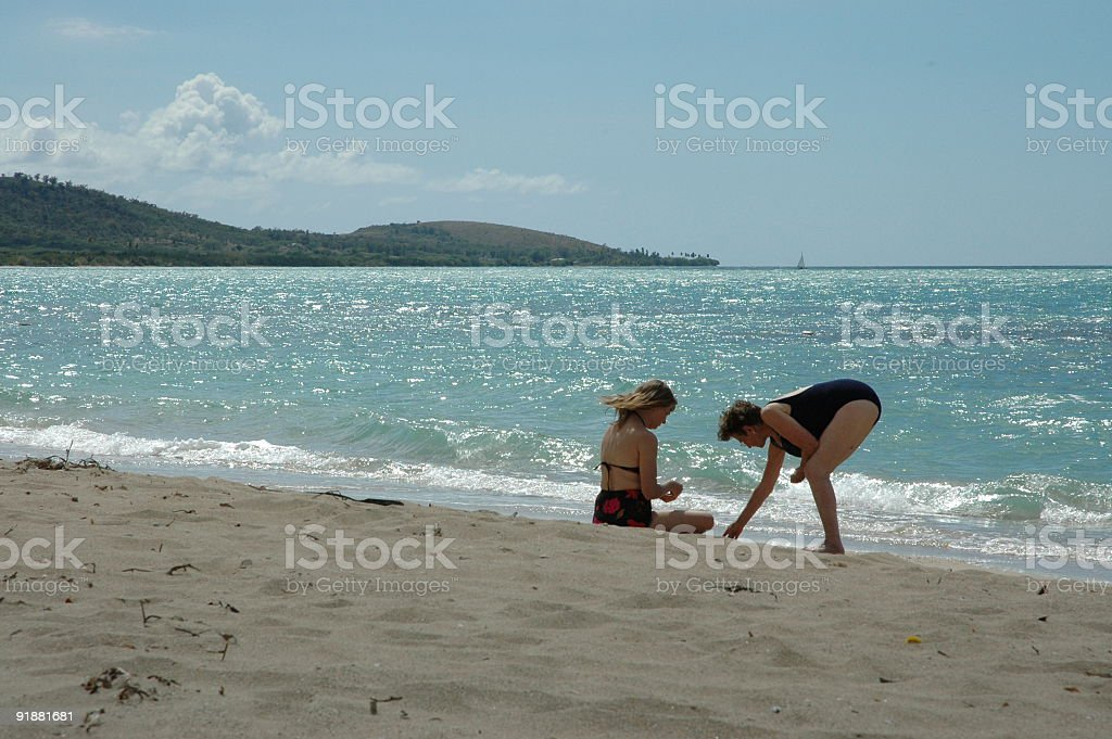 Two women relaxing on the beach stock photo