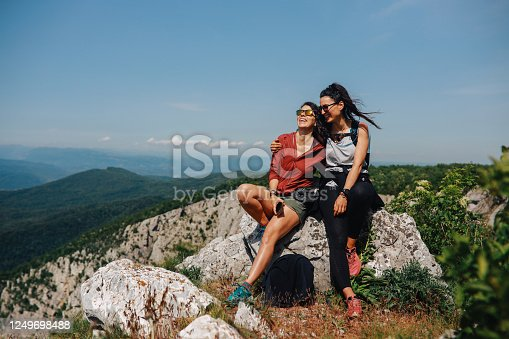 Two young female hikers resting on top of the mountain.