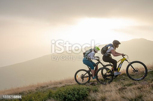 istock Two women ride up grassy hillside on electric mountain bikes 1223716894