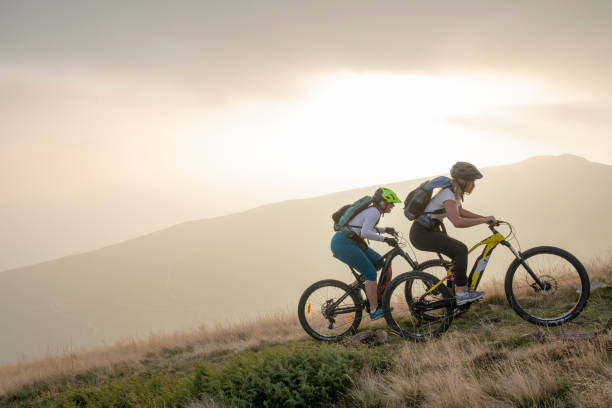 Two women ride up grassy hillside on electric mountain bikes Sun sets over distant mountain range electric bike stock pictures, royalty-free photos & images
