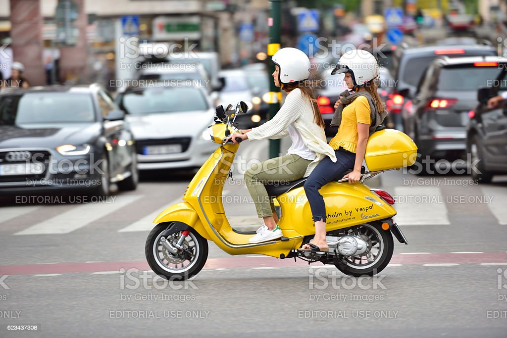 Two women riding vespa in central stockholm stock photo
