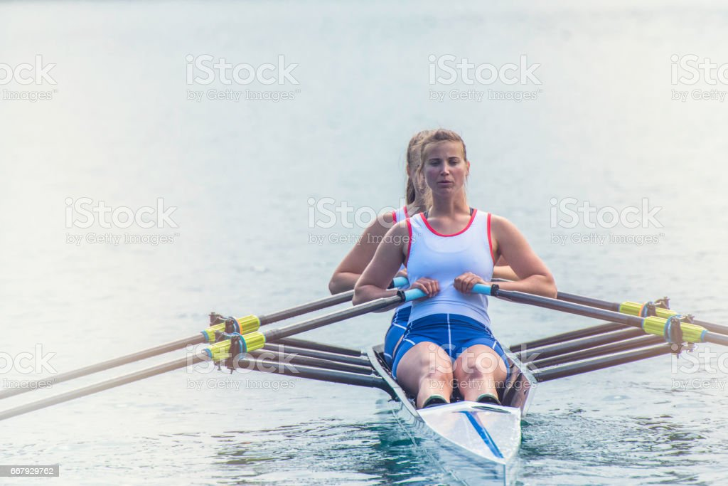 Two women rowing on a lake stock photo
