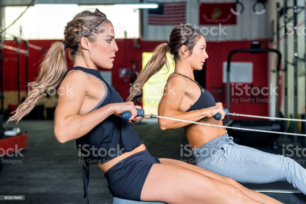Zwei Frauen Rudern mit macht in Turnhalle – Foto