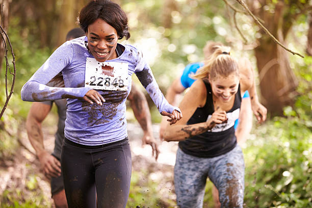 two women running in a forest at an endurance event - obstacle run stockfoto's en -beelden