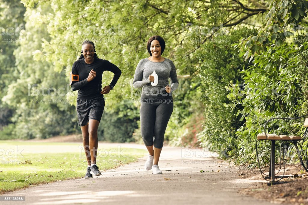 Two women running in the park stock photo