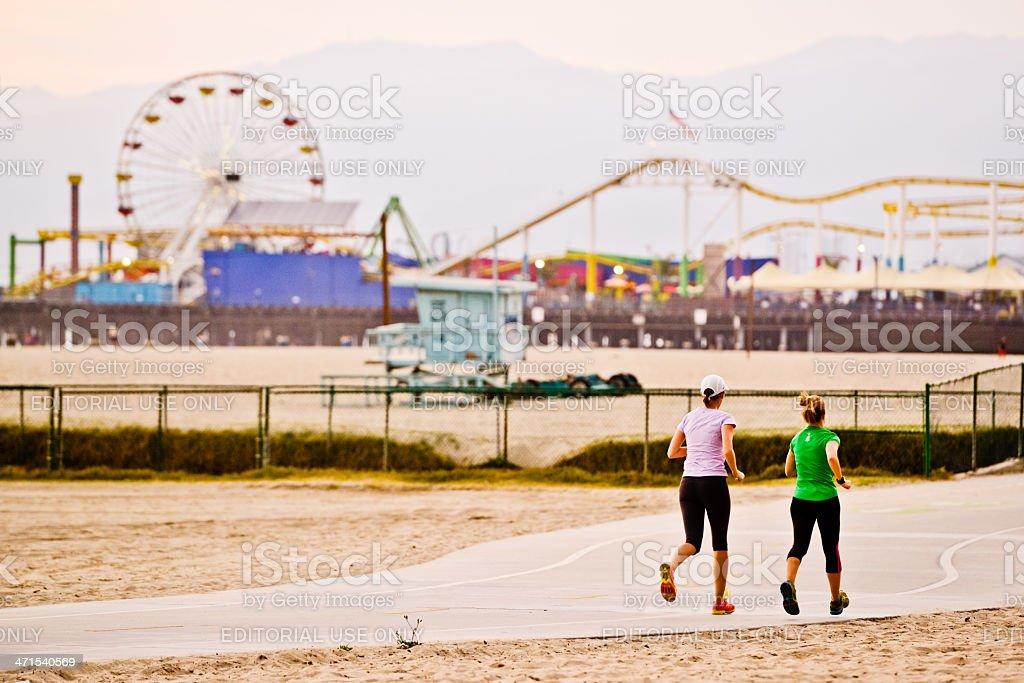 Two women running on Santa Monica beach royalty-free stock photo