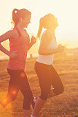 Two women running together in the park. They are exercising at sunset or sunrise with the city of Sydney in the background. One has a smart phone on her arm and is listening to music. Copy space. They are smiling and happy having fun.