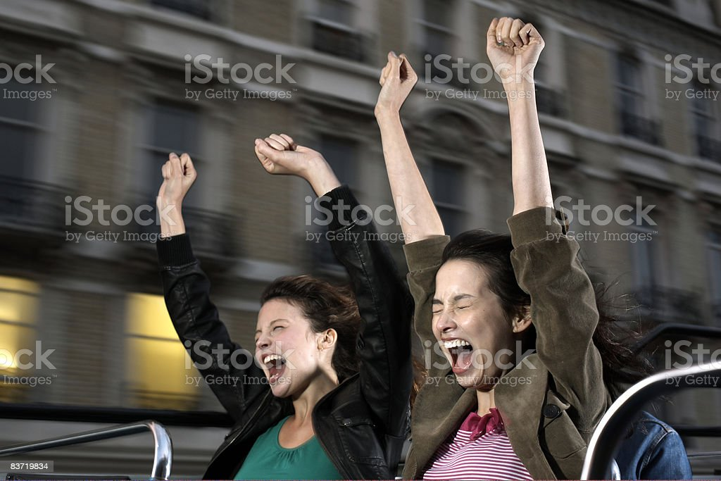 Two women screaming on open top bus  royaltyfri bildbanksbilder