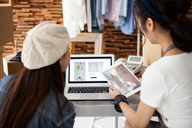 Two women selling clothes at online shopping stock photo