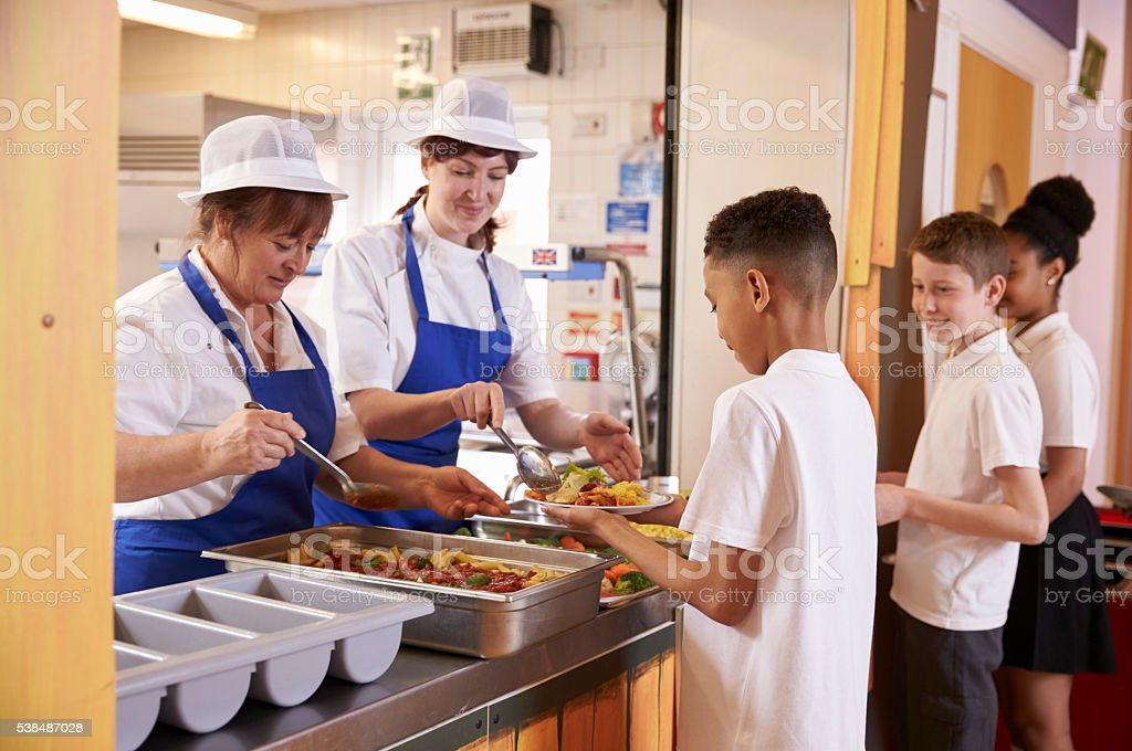 Two women serving food to a boy in a school cafeteria stock photo
