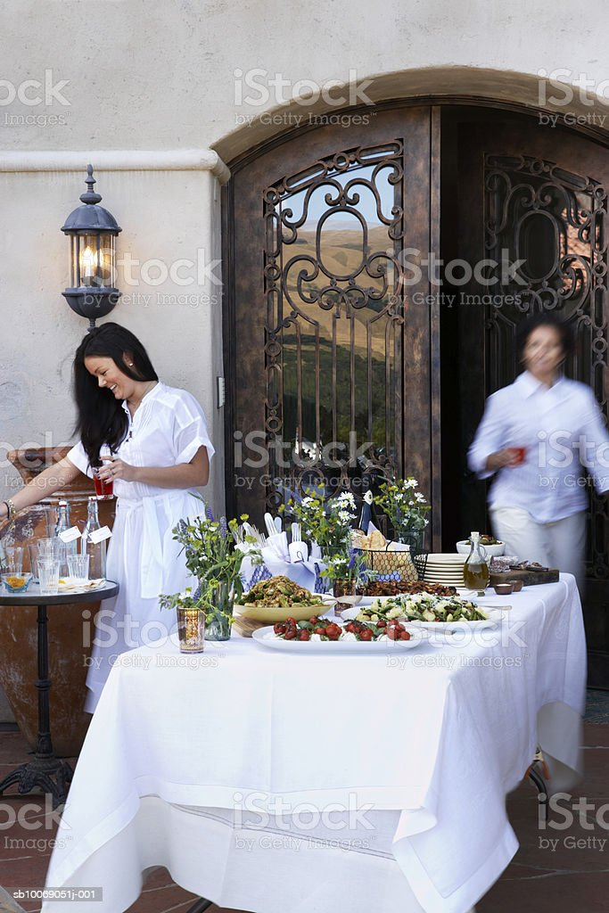 Two women setting table of appetizers, wrought iron door in background royalty free stockfoto