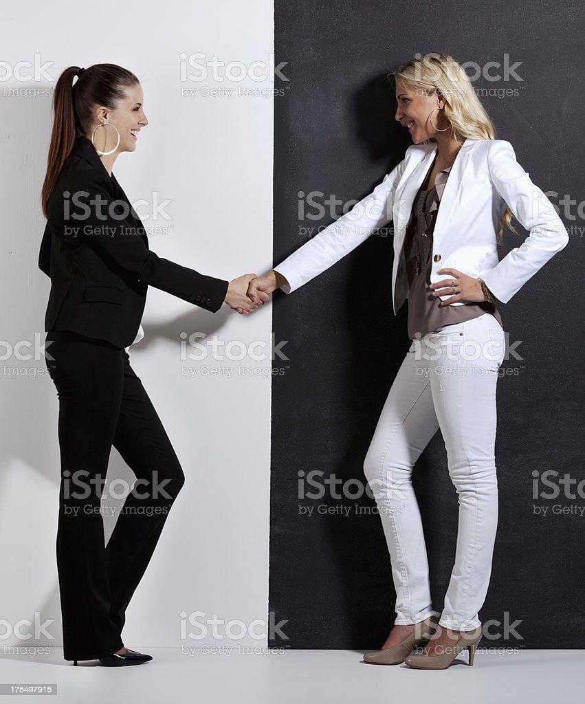 Two women shaking hands stock photo