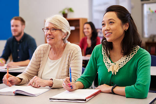 Two women sharing a desk at an adult education class Two women sharing a desk at an adult education class look up adult student stock pictures, royalty-free photos & images